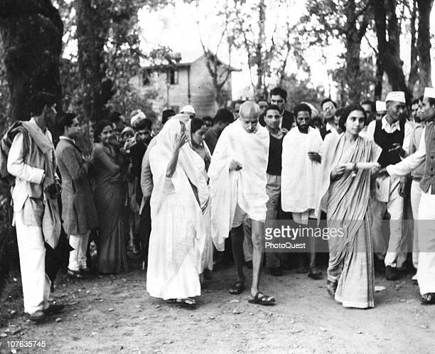 Indian political and social leader Mohandas K Gandhi and a nubers of others walk mid to late 1930s