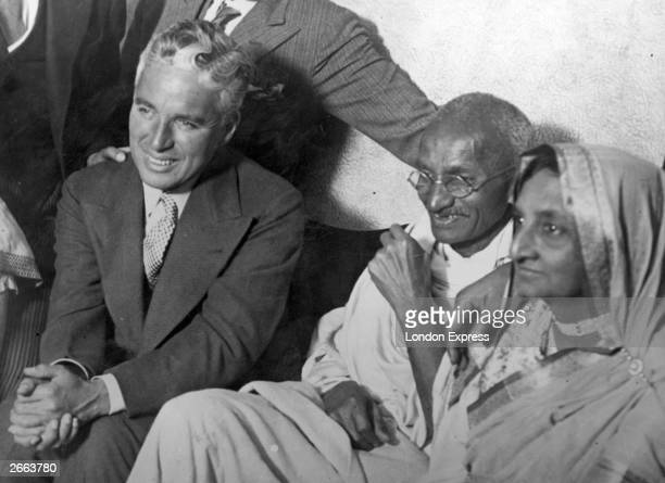 Indian political and spiritual leader Mahatma Gandhi centre and his wife meet film actor Charlie Chaplin at the home of Dr Katral in Canning Town...