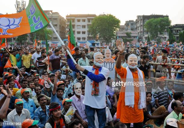 Indian political supporters of of Bharatiya Janata Party wave a party flag as they wear masks of Prime Minister Narendra Modi during an election...
