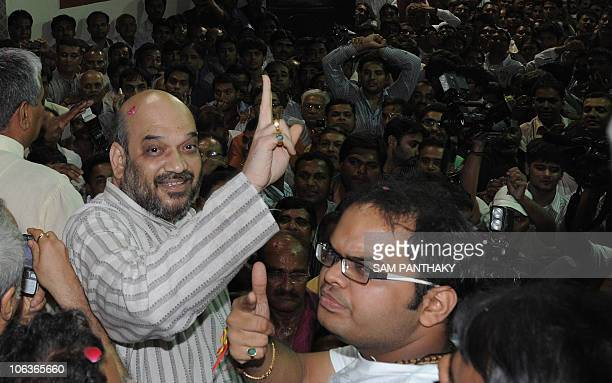 Indian politician and former Gujarat minister Amit Shah and his son Jay celebrate on his arrival at his residence after his release from Sabarmati...