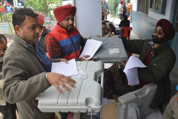 Indian poll officials carry Electronic Voting Machines from a distribution centre in Amritsar on February 3 2017 State Assembly elections are...