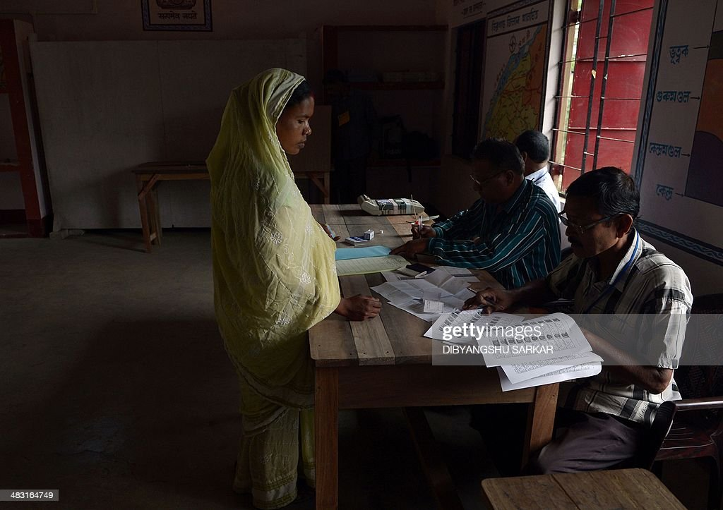 Indian polling officials check the details of Santoshi Bhumej (C) the first voter who entered the polling booth to cast her vote in Dibrugarh on April 7, 2014, during national elections. Indians have begun voting in the world's biggest election which is set to sweep the Hindu nationalist opposition to power at a time of low growth, anger about corruption and warnings about religious unrest. India's 814-million-strong electorate are forecast to inflict a heavy defeat on the ruling Congress party, in power for 10 years and led by India's famous Gandhi dynasty. AFP PHOTO/Dibyangshu SARKAR