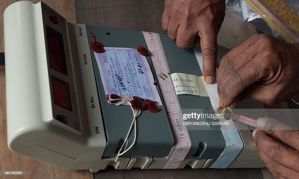 Indian polling officials seal an Electronic Voting Machine (EVM) infront of polling agents prior to the start of voting at a polling station in Dibrugarh on April 7, 2014, as they prepare for voters arrival during national elections. Indians have begun voting in the world's biggest election which is set to sweep the Hindu nationalist opposition to power at a time of low growth, anger about corruption and warnings about religious unrest. India's 814-million-strong electorate are forecast to inflict a heavy defeat on the ruling Congress party, in power for 10 years and led by India's famous Gandhi dynasty. AFP PHOTO/ Dibyangshu SARKAR