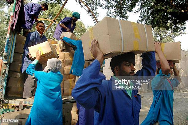 Indian porters unload boxes of dry fruits from Pakistani trucks at The Wagah Border Post 03 October 2007 For the first time since the border was...