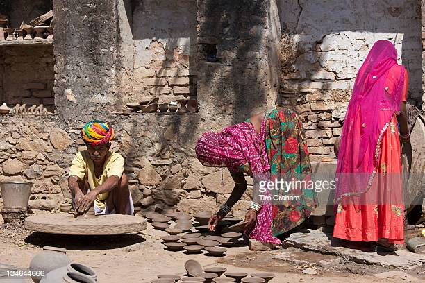 Indian potter in traditional Rajasthani turban works at home with his family making clay pots in village of Nimaj Rajasthan Northern India