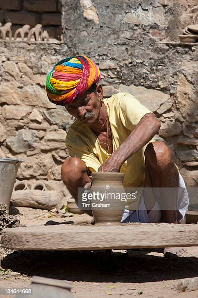 Indian potter in traditional Rajasthani turban works on potter's wheel at home making clay pots in Nimaj village Rajasthan Northern India