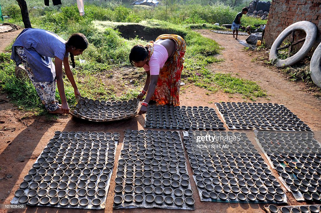 Indian potters arrange earthenware oil pots or 'diyas' to dry in the sun at a workshop on the outskirts of Hyderabad on October 25, 2010, prior to the Diwali Festival - Festival of Lights - which will be celebrated on November 5. Diyas, which are lit and placed around the home, are in heavy demand during the festival which marks the victory of good over evil and commemorates the time when Hindu God Lord Rama achieved victory over Ravana and returned to his Kingdom Ayodhya after 14 years of exile. AFP PHOTO/Noah SEELAM