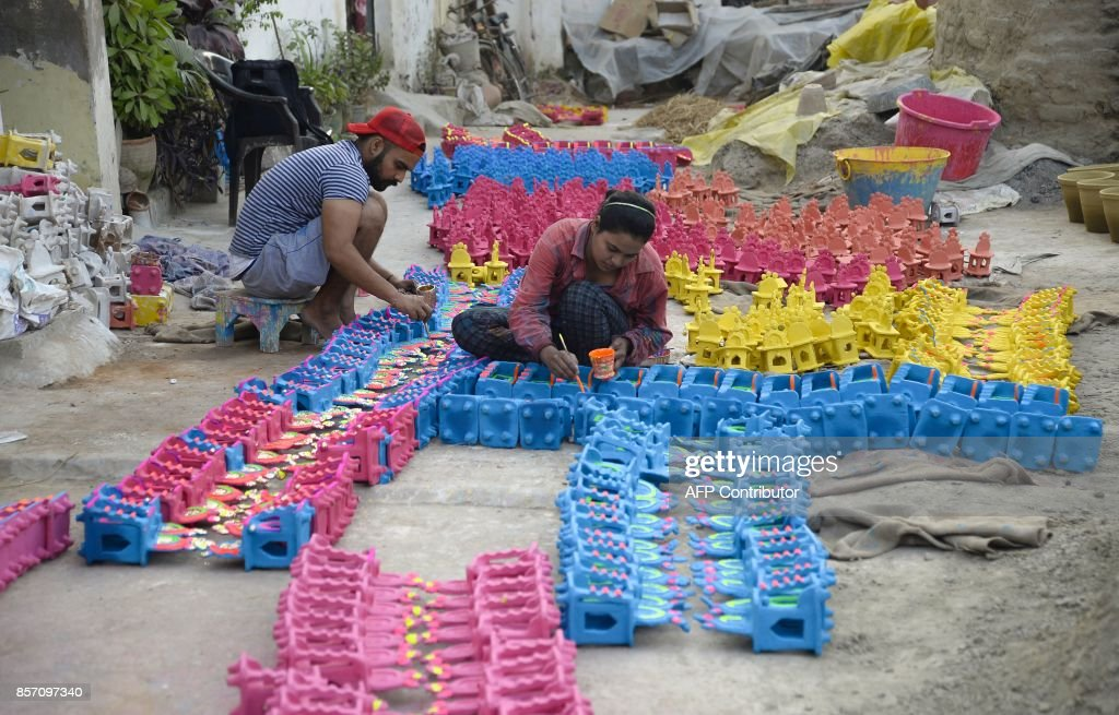 Indian potters paint earthen lamps ahead of the Hindu festival of Diwali in Jalandhar on October 3 2017 Diwali the Festival of Lights marks victory...