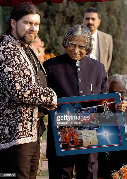 Indian President A P J Abdul Kalam receives a framed memento from Jean Pierre Harrison the husband of late Indianborn astronaut Kalpana Chawla who...