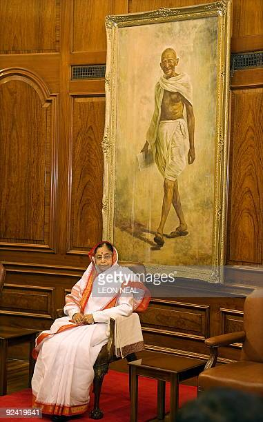Indian President Pratibha Patil sits in front of a portrait of Mahatma Gandhi before being presented with a collection of his letters during a...