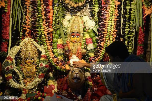 Indian priests offer prayers to a statue of the Hindu goddess Mahakali decorated with vegetables ahead of the Bonalu festival at Sri Ujjaini Mahakali...