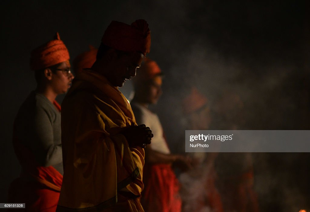 Indian priests play a shell instruement as they perform an evening prayer, on the banks of Holy sangam, confluence of Ganges,yamuna and Mythical Saraswati river, in Allahabad on December 11,2016.