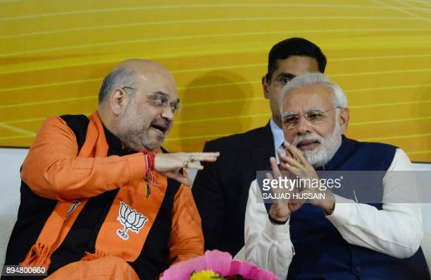 Indian Prime Minister and head of the Bharatiya Janata Party Narendra Modi and party president Amit Shah talk at the start of a speech at the party...