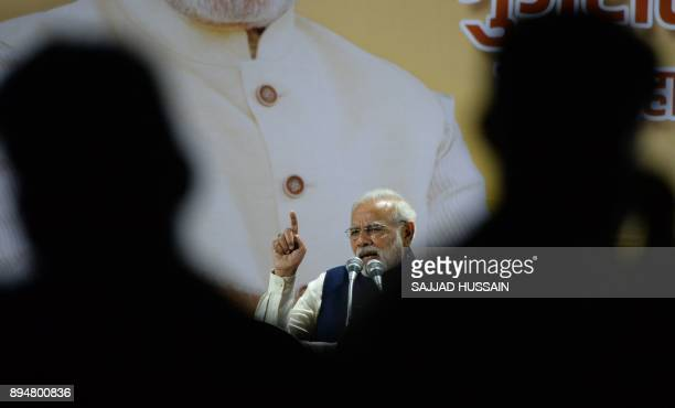 Indian Prime Minister and head of the Bharatiya Janata Party Narendra Modi gestures as he speaks at the party headquarters in New Delhi on December...
