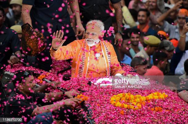 TOPSHOT Indian Prime Minister and leader of the Bharatiya Janata Party Narendra Modi gestures during a roadshow in Varanasi on April 25 2019 Tens of...