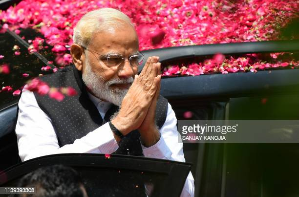 Indian Prime Minister and leader of the Bharatiya Janata Party Narendra Modi gestures to supporters as he arrives to file his election nomination...