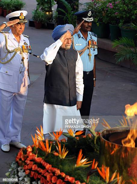 Indian Prime Minister Manmohan Singh along with Indian Navy chief admiral Sureesh Mehta and an unidentified senior Air Force officer salute at India...