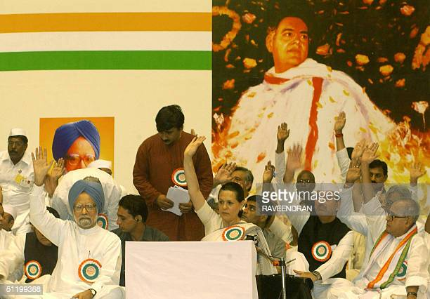 Indian Prime Minister Manmohan Singh Congress Party President Sonia Gandhi and AICC members hold their hands up during the inauguration ceremony for...