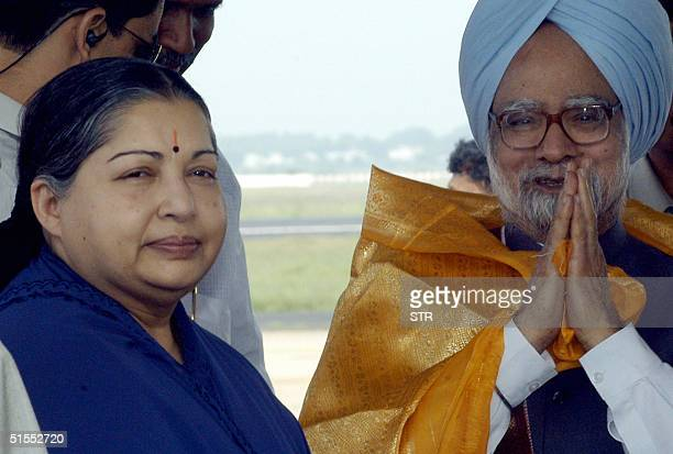 Indian Prime Minister Manmohan Singh greets unseen people as the chief minister of India's southern state of Tamil Nadu J Jayalalithaa looks on upon...