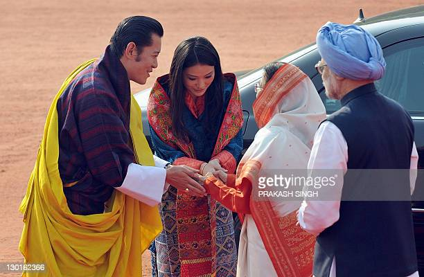 Indian Prime Minister Manmohan Singh watches as Bhutan's King Jigme Khesar Namgyel Wangchuck introduces his newlywed Queen Jetsun Pema to Indian...