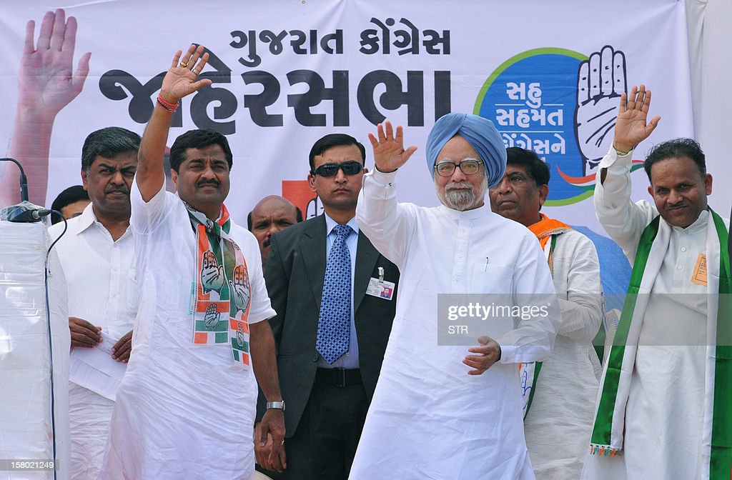 Indian Prime Minister, Manmohan Singh (C) waves as arrives on stage to address a political rally in support of Congress Party at Vansda town, some 350 kms from Ahmedabad on December 9, 2012. Gujarat state goes to polls in two phases, December 13 and 17, 2012.