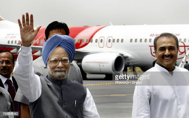 Indian Prime Minister Manmohan Singh waves as Civil Aviation Minister Praful Patel looks on, after the launch of Air India's fleet at the Air Force...