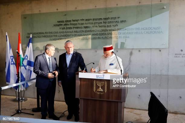 Indian Prime Minister Narendra Modi accompanied by Israeli Prime Minister Benjamin Netanyahu and Yad Vashem Chairman Avner Shalev sign the guest book...