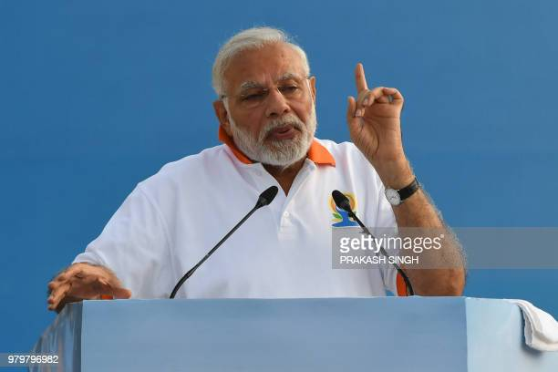 Indian Prime Minister Narendra Modi addresses participants before a mass yoga session along with other practitioners to mark International Yoga Day...