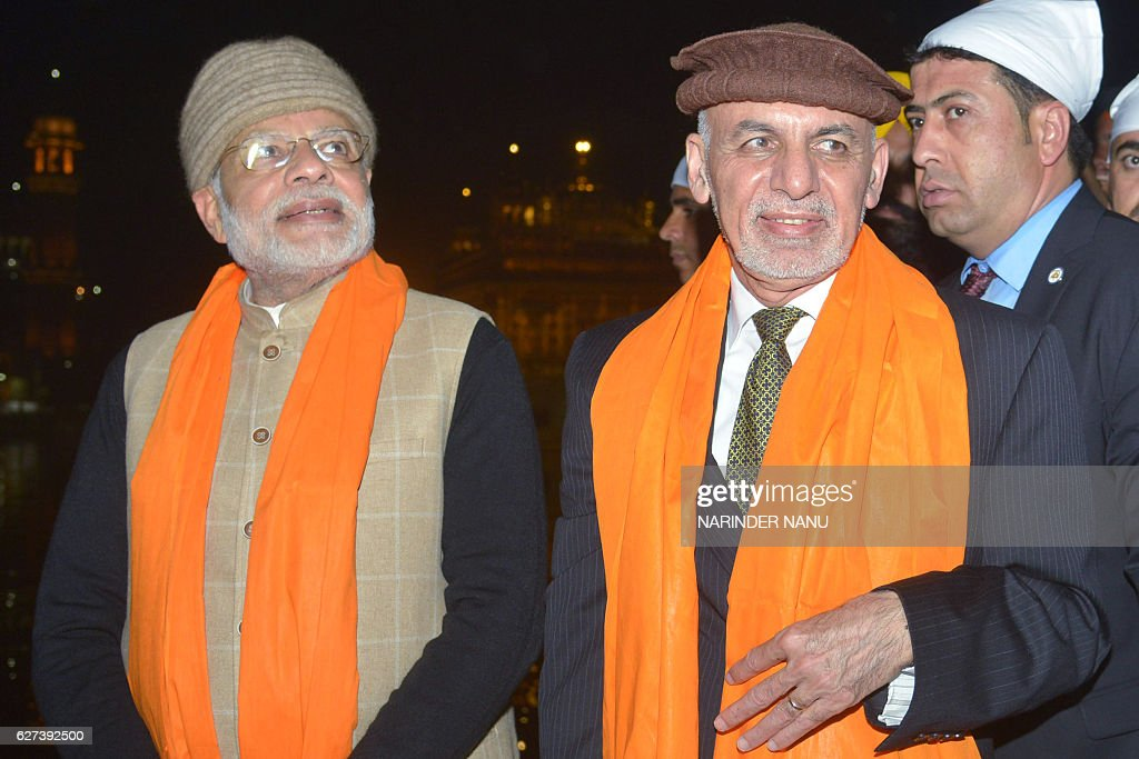 Indian Prime Minister Narendra Modi Afghan President Ashraf Ghani pay respects at the Golden temple in Amritsar on December 3 2016 Modi visited the...