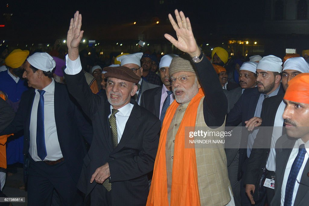 Indian Prime Minister Narendra Modi and Afghan President Ashraf Ghani gestures during their visit at the Golden temple in Amritsar on December 3 2016.