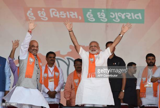 Indian Prime Minister Narendra Modi and Bhartiya Janta Party President Amitbhai Shah wave to the supporters on their arrival at Gujarat Gaurav...