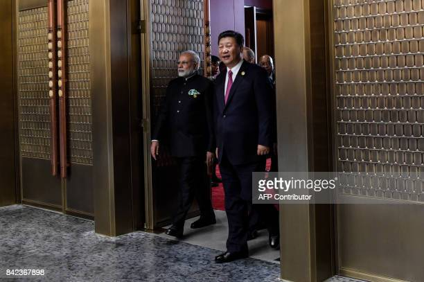 Indian Prime Minister Narendra Modi and Chinese President Xi Jinping arrive at the plenary session during the BRICS Summit at the Xiamen...
