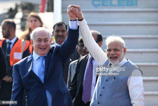 Indian Prime Minister Narendra Modi and Israeli Prime Minister Benjamin Netanyahu pose for photographers after NEtanyahu arrived at the Air Force...