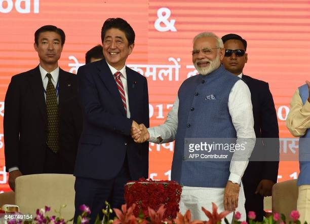Indian Prime Minister Narendra Modi and Japan's Prime Minister Shinzo Abe shake hands during a ground breaking ceremony for the MumbaiAhmedabad high...