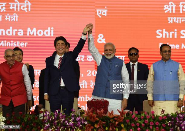 Indian Prime Minister Narendra Modi and Japan's Prime Minister Shinzo Abe hold hands during a ground breaking ceremony for the MumbaiAhmedabad high...