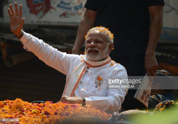 Indian Prime Minister Narendra Modi and Leader of the Bharatiya Janata Party waves during a roadshow in support of state assembly election party...