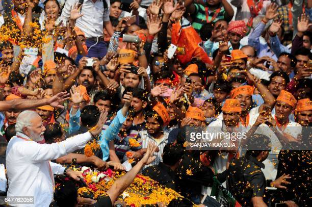 Indian Prime Minister Narendra Modi and leader of the Bharatiya Janata Party gestures during a roadshow in support of state assembly election party...