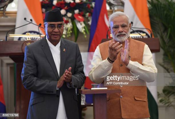 Indian Prime Minister Narendra Modi and Nepali Prime Minister Sher Bahadur Deuba applaud while dedicating IndiaNepal two 132KV power transmission...