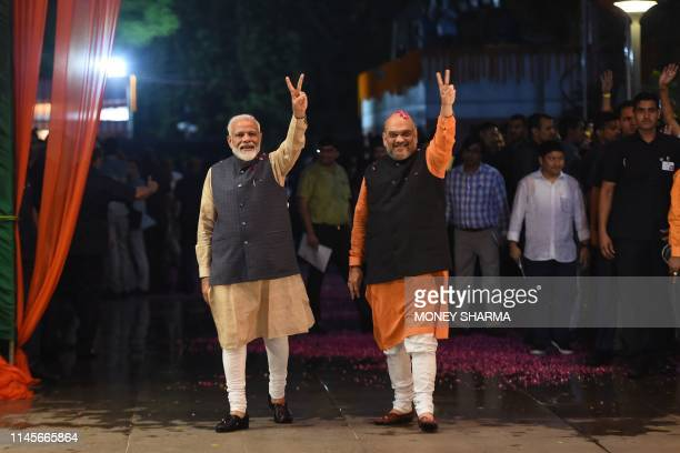 Indian Prime Minister Narendra Modi and president of the ruling Bharatiya Janata Party Amit Shah gesture as they celebrate the victory in India's...