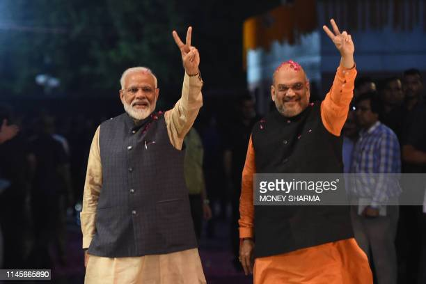 TOPSHOT Indian Prime Minister Narendra Modi and president of the ruling Bharatiya Janata Party Amit Shah gesture as they celebrate the victory in...