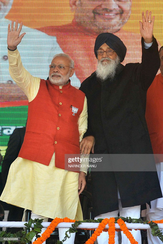 Indian Prime Minister Narendra Modi and Punjab Chief Minister Parkash Singh Badal wave to supporters during the Bharatiya Janata Party rally at the...