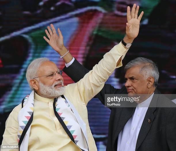 Indian Prime Minister Narendra Modi and Sri Lankan Prime Minister Ranil Wickremesinghe wave to Sri Lankan tea plantation workers of Indian origin...