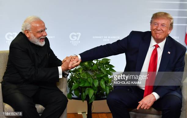 TOPSHOT Indian Prime Minister Narendra Modi and US President Donald Trump shakes hands as they speak during a bilateral meeting in Biarritz southwest...
