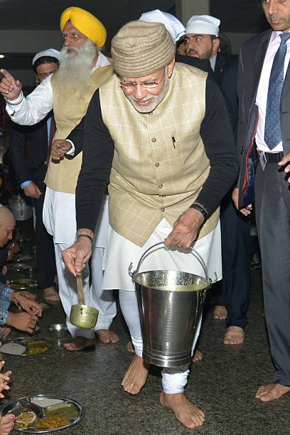 Indian Prime Minister Narendra Modi distributes food known as `langar` vegetarian meals distributed free of charge to all who attend during his visit.