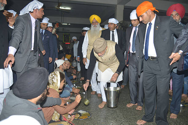 Indian Prime Minister Narendra Modi distributes free food known as `langar` vegetarian meals to devotees during his visit at the Golden temple in...