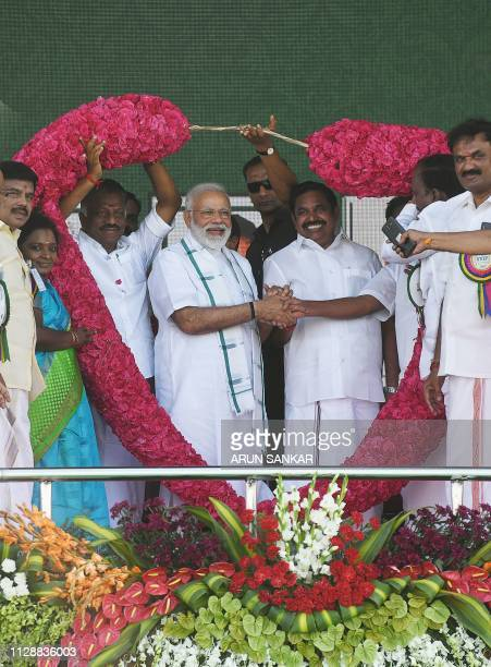 Indian Prime Minister Narendra Modi gestures as he is garlanded by Indian Chief Minister of the state of Tamil Nadu Edappadi Palanisamy during a...