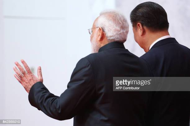 Indian Prime Minister Narendra Modi gestures as he talks with Chinese President Xi Jinping as they arrive for a group photo during the BRICS Summit...
