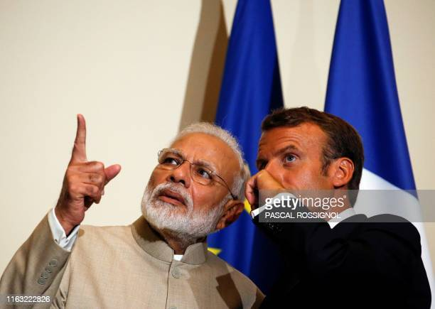 Indian Prime Minister Narendra Modi gestures next to French President Emmanuel Macron during their joint statement following a meeting at the Chateau...