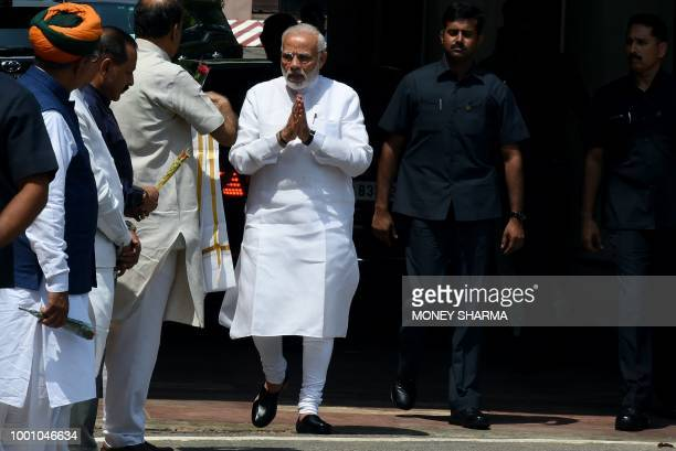 Indian Prime Minister Narendra Modi gestures to senior Bharatiya Janata Party leaders after arriving for the monsoon session of Parliament in New...