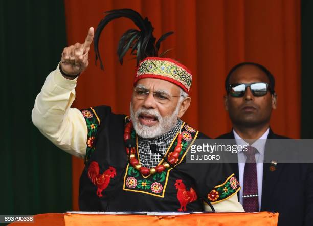 Indian Prime Minister Narendra Modi gestures while addressing a Bharatiya Janata Party rally dressed in traditional Khasi tribe attire and Garo tribe...